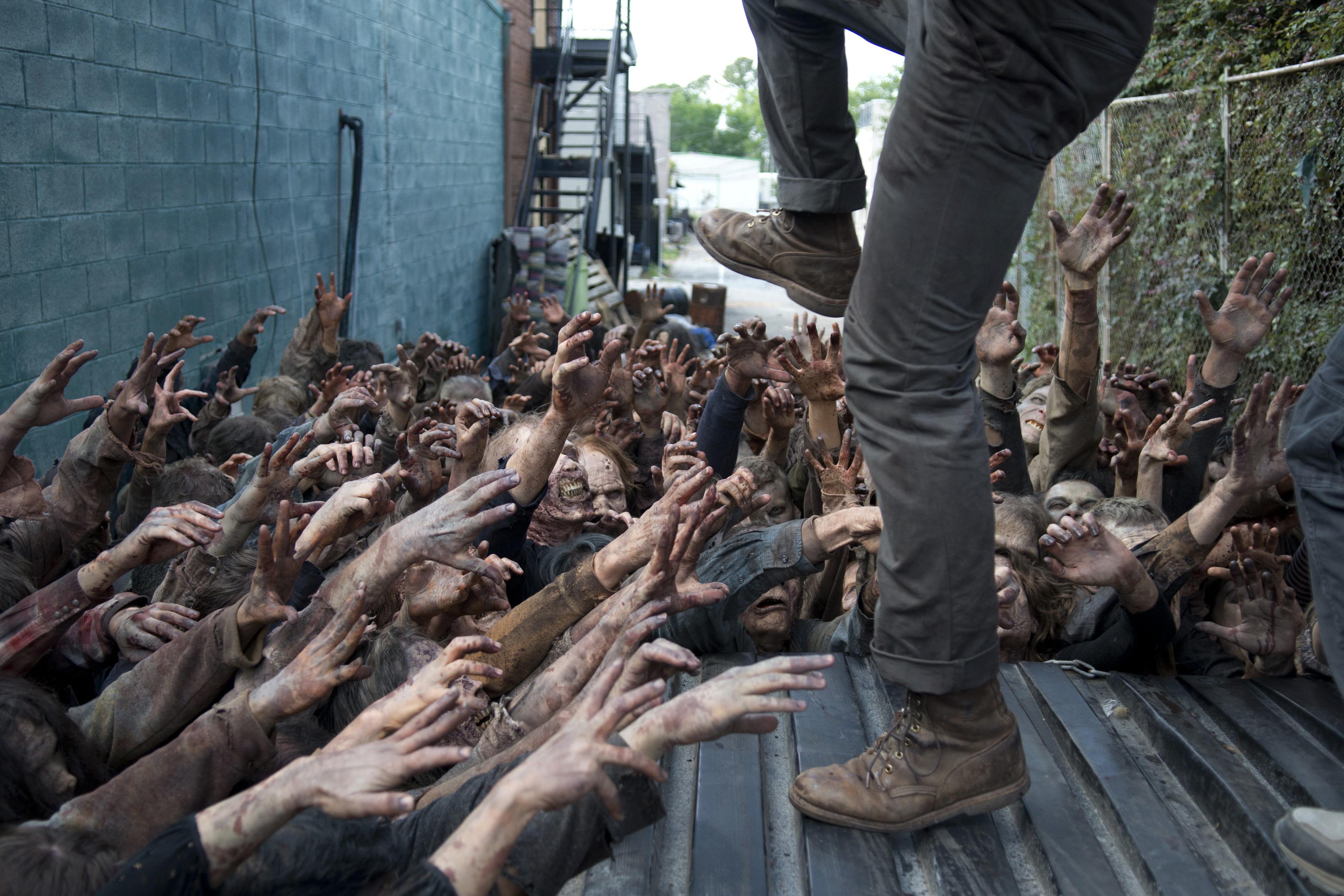 Walkers grab at glenn in the walking dead season 6.